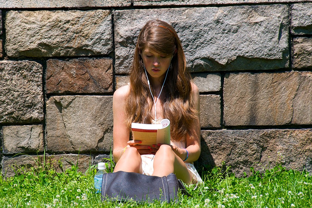 1080px-Cute_girl_reading_outdoors.jpg
